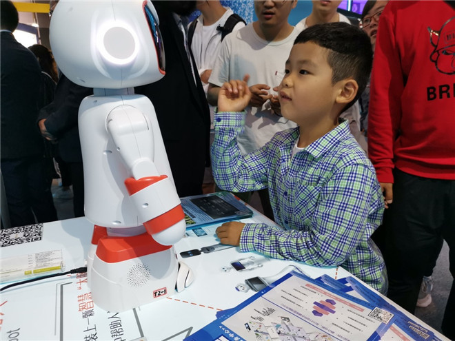 小朋友在数博会展馆和智能机器人对话 董贤武/摄